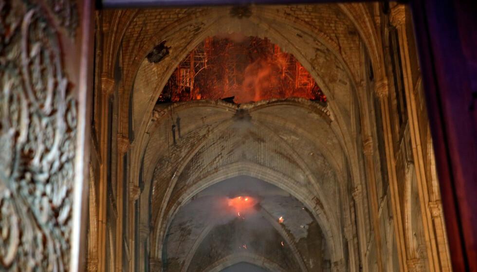 BRANN I TAKET: Flammer og røyk på innsiden av Notre-Dame. Foto: REUTERS/Philippe Wojazer/Pool