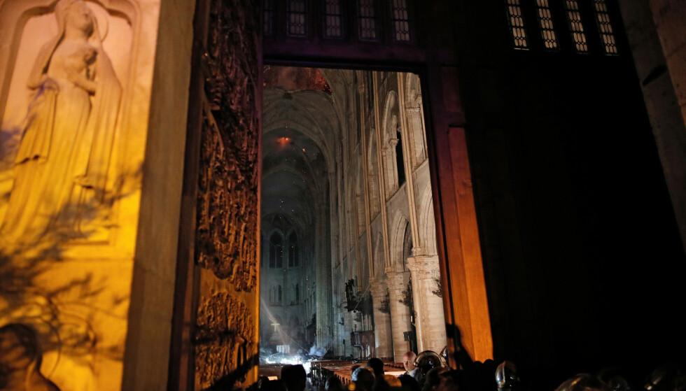 INNGANG: Bilde fra inngangspartiet viser hvordan røyk stiger opp rundt alteret i Notre-Dame. REUTERS/Philippe Wojazer/Pool