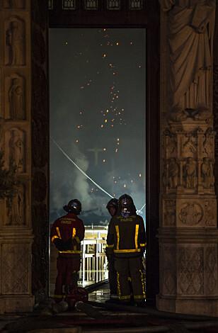 SLUKKER: Brannmenn forsøker å slukke brannen i Notre-Dame. Foto: Eliot Blondet/ABACAPRESS.COM