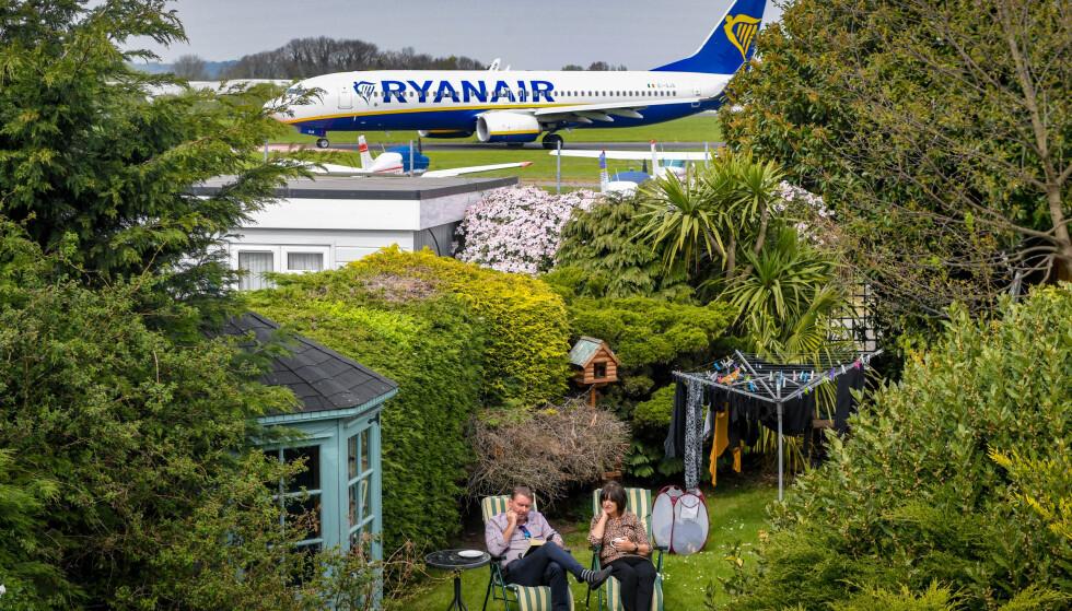 «MARERITT»: Alex og June Carr avbildet i hagen sin med et Ryanair-fly på rullebanen noen meter lenger unna. Naboene til London Southend flyplass beskriver sin nye hverdag med jetfly «i hagen» som et mareritt. Foto: SWNS