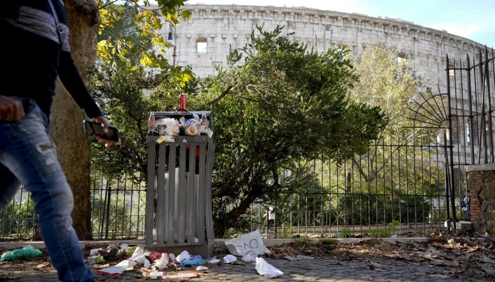 SØPPEL: Selv turistene i Roma begynner nå å reagere på hvorfor de blir avkrevd skatt, mens søppelet flyter i Roma - og forfallet fortsetter. Her Colosseum i bakgrunnen. Foto: AP / NTB Scanpix