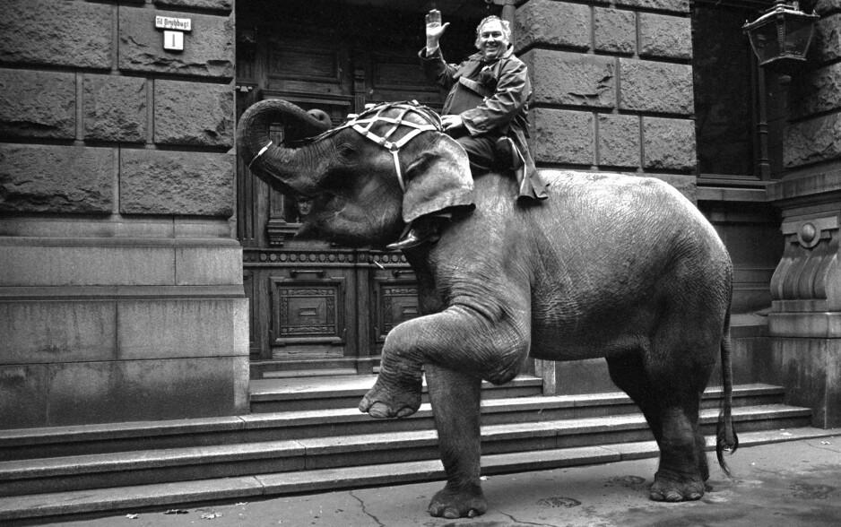 ARNE ANDERSEN alias Arnardo var en spreder av glede og godt humør gjennom sin lange karriere som sirkusdirektør. Her er han på vei til Tinghuset der han vil føre elefanten som vitne i en rettssak. Dyret fikk ikke tillatelse til å ta plass i vitneboksen. Foto: NTB Scanpix