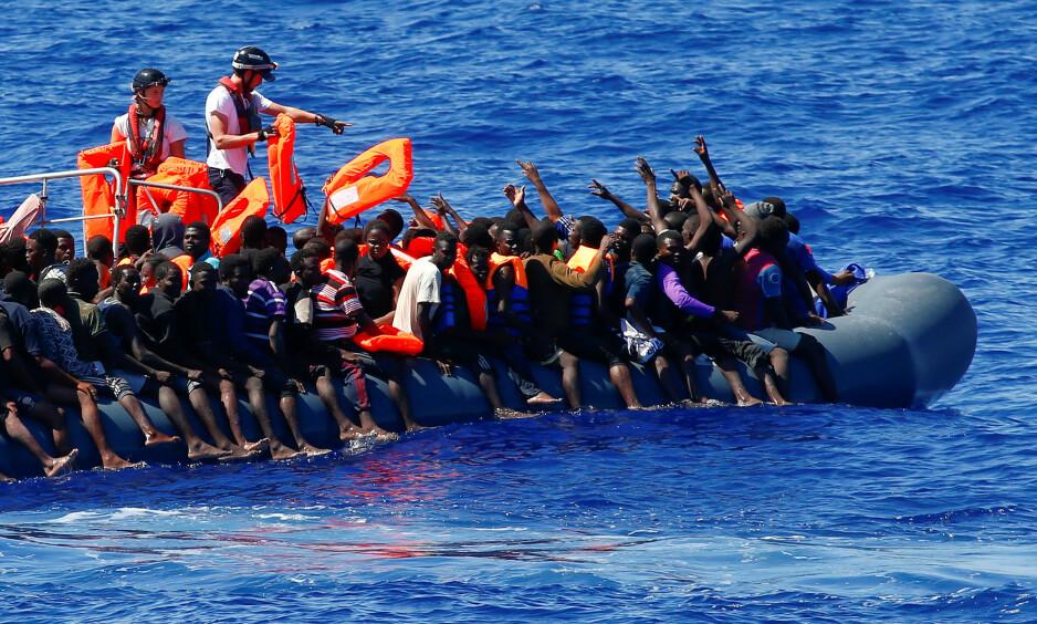 HUMANITÆR INNSATS: Flyktninger og migranter reddes av NGO-en SOS Mediterranée utenfor den libyske kysten. Denne innsatsen skal nå straffes dersom Italias innenriksminister får det som han vil. Foto: Tony Gentile / Reuters / NTB Scanpix