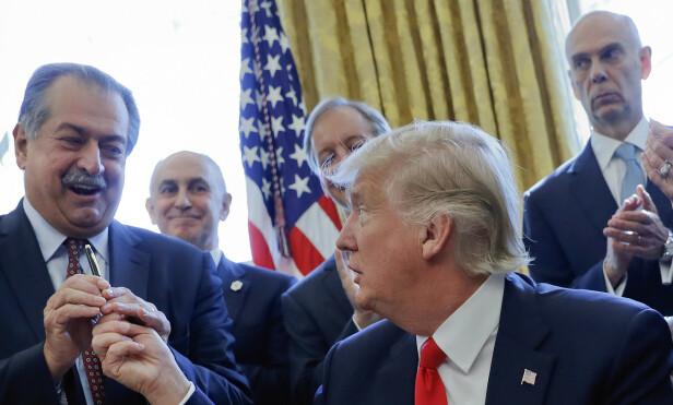 DOW CHEMICAL OG TRUMP: President Donald Trump gir pennen sin til Dow Chemicals styreleder og direktør, Andrew Liveris, etter at å ha signert en presidentordre. Rundt dem applauderer andre næringslivsledere. Foto: Pablo Martinez Monsivais/AP