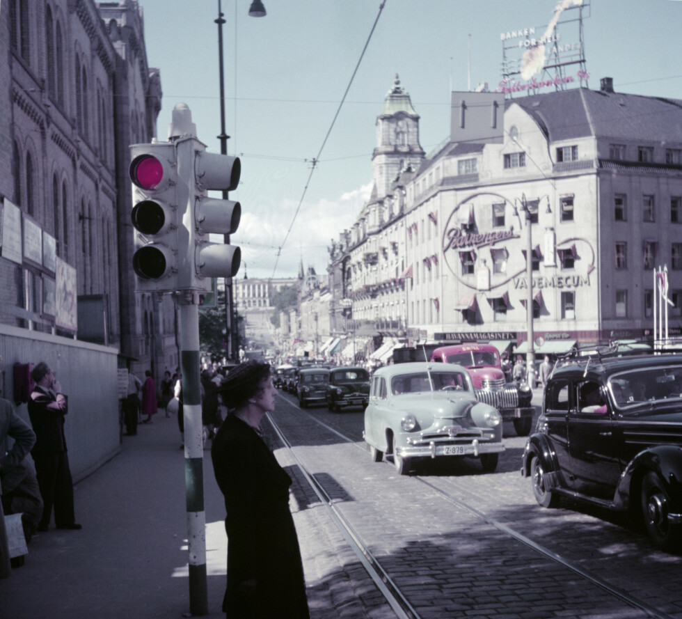 Oslo 1950 ( ca ) Karl Johan 's gate med mennesker, biler. Trikkeskinner. Reklameskilt på Grand Hotel gården: Fellesbanken, Vademecum fra Barnengen. FOTO: Camera Press / Billedsentralen  / SCANPIX