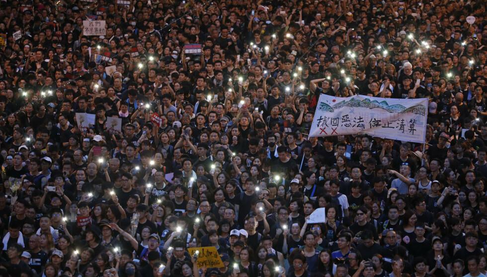 DEMONSTRASJON: Mobiltelefonlykter lyser opp demonstrasjonen i Hongkong søndag. Foto: Vincent Yu / AP / NTB scanpix