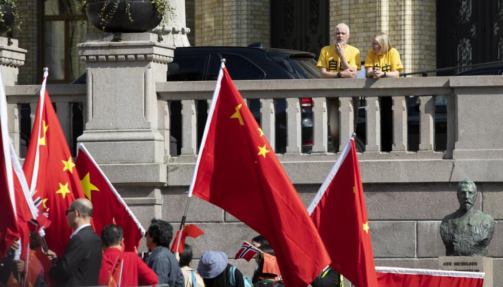 """PROPAGANDA: Kineserne ville ta fine bilder foran Stortinget. Representantene Petter Eide (SV) og Guri Melby (V) hadde på seg gule T-skjorter med påskriften """"Frihet"""" på kinesisk. Foto: Ryan Kelly / NTB scanpix"""