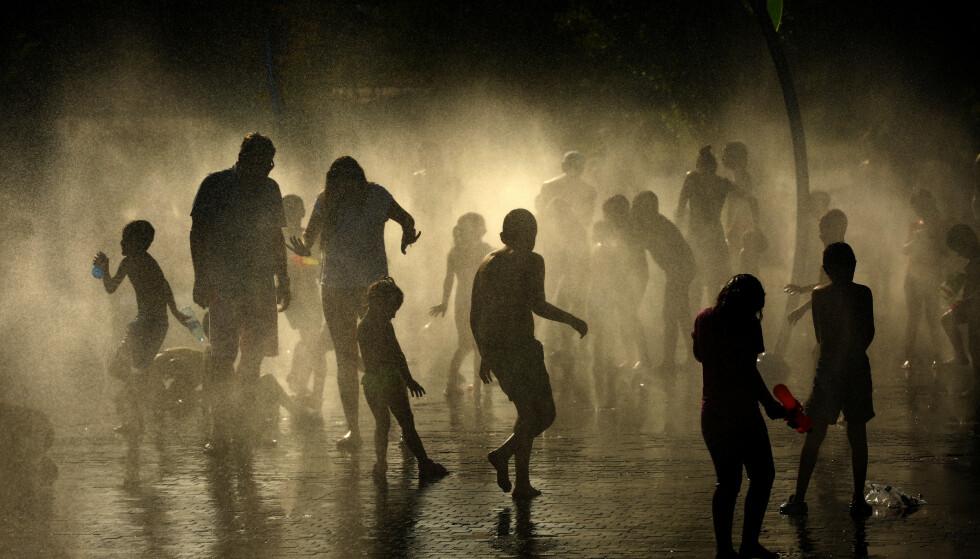 HETEBØLGE: Barn og unge kjøler seg ned i Rio-parken i Madrid. Foto: AP / NTB scanpix