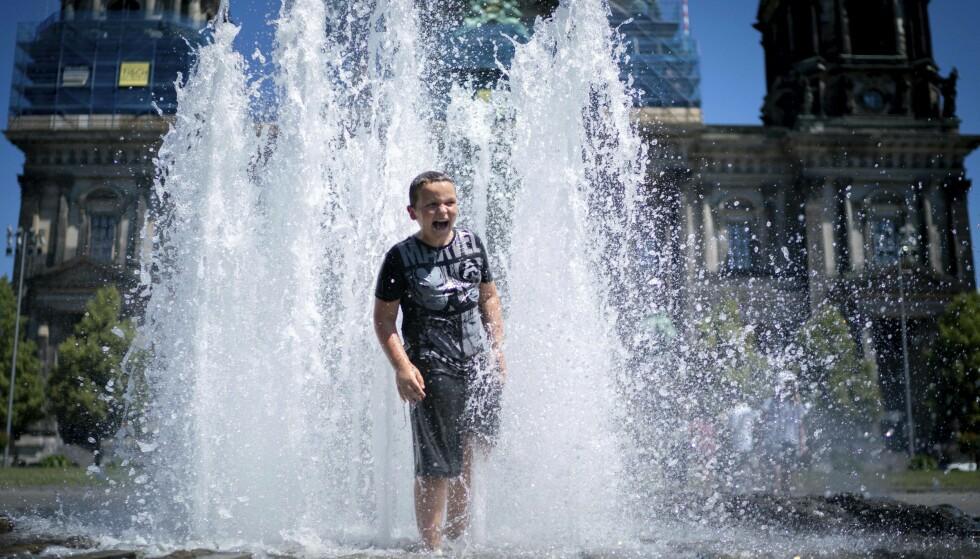 HETT: Berlin hadde søndag temperaturer opp mot 39 grader. Her kjøler en gutt seg ned i en fontene i den tyske hovedstaden. Hetebølgen er avtakende i Tyskland de neste dagene. Foto: Kay Nietfeld/dpa via AP/NTB Scanpix