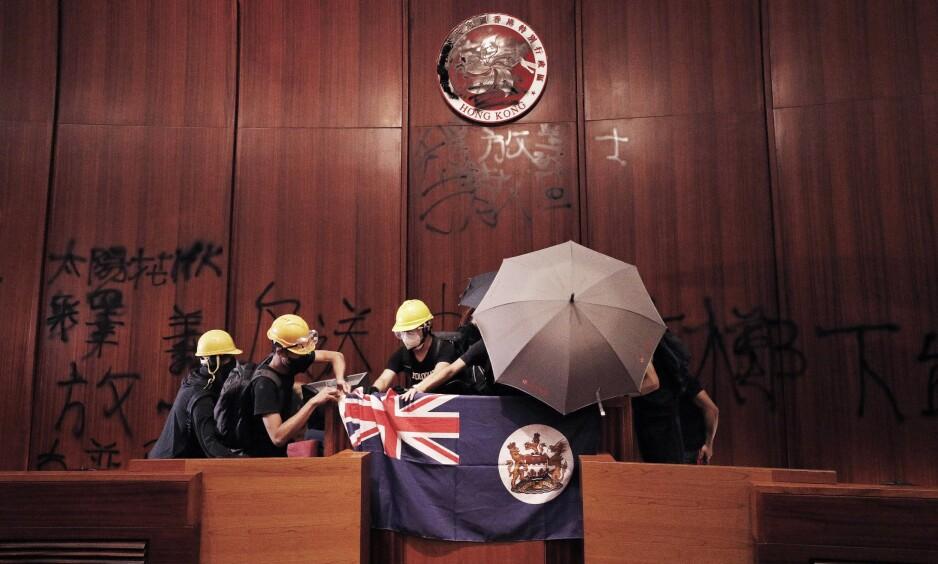 KOLONIFLAGGET: Aksjonister henger opp det gamle britiske koloniflagget inne i forsamlingssalen i Hongkongs parlament. På veggen bak er regionens nåværende flagg tilgriset. Foto: Vincent Yu / AP / NTB Scanpix