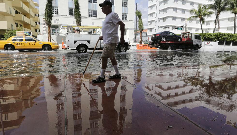 VÅTT: Louis Fernandez spaserer på en oversvømt gate i Miami Beach. Slike oversvømmelser vil bli stadig vanligere med stigende havnivå. Foto: Lynne Sladky / AP / NTB Scanpix