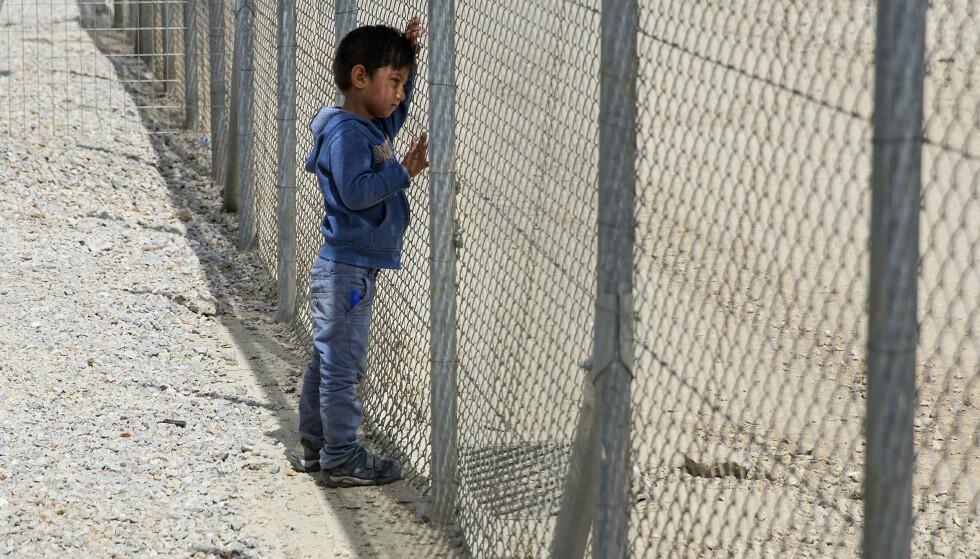MORIA: En liten gutt lener seg mot gjerdet som omringer Moria-leiren på Lesvos. Bildet er fra 2016, men fortsatt bor mange i flyktningleieren på den greske øya. Foto: Tore Meek / NTB scanpix
