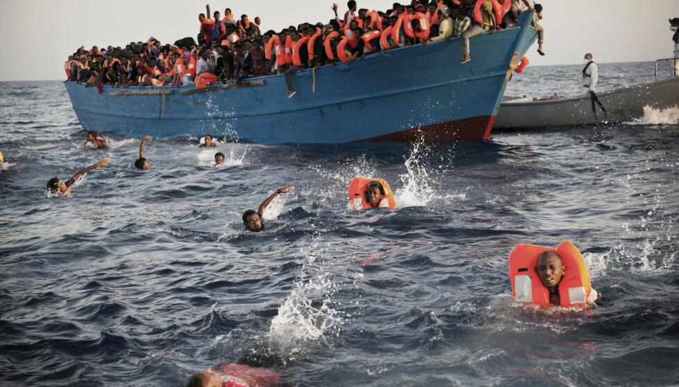 MIGRANTER: Migranter, de fleste her fra Eritrea, hopper i vannet fra en overfylt trebåt under en redningsoperasjon i Middelhavet utenfor kysten av Libya i 2016. Foto: Emilio Morenatti / AP / NTB Scanpix
