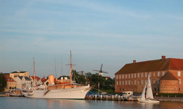 KONGESKIP: Her ligger «Dannebrog» i havn i Søndeborg. Til høyre ser man sjøsiden av Sønderborg Slott. Foto: Wikimedia Commons.