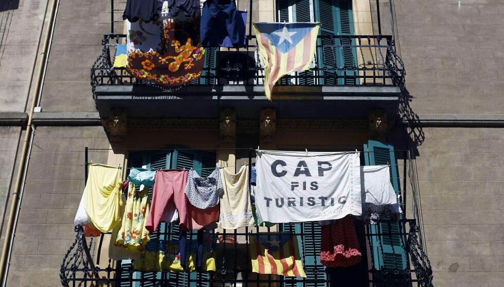 INNVANDRINGSTAK: På en balkong i bydelen Barceloneta i Barcelona henger et krav om tak på antallet korttidsutleide leiligheter. Innbyggerne vil ha en slags innvandringsstopp for rike utlendinger som ødelegger byen under sine kortvarige opphold. Foto: Quique García / AFP / NTB Scanpix