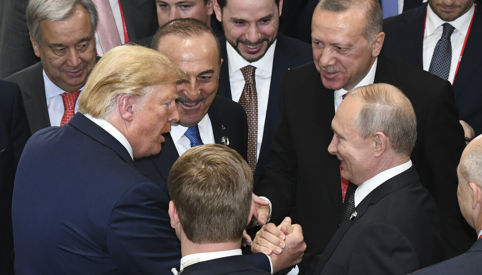 KRAFTIG HÅNDTRYKK: Donald Trump hilser på Vladimir Putin, mens Tyrkias president Recep Tayyip Erdogan (øverst til høyre) ser på, under G-20 møtet i Japan i juni. Foto: AP / NTB Scanpix