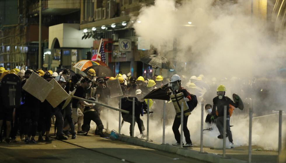 TÅREGASS OG GUMMIKULER: Protestanter barker sammen med politiet i Hongkong. Foto: Vincent Yu / NTB Scanpix.