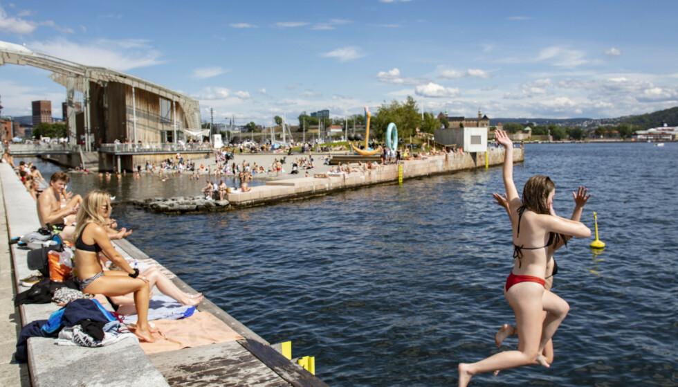 HOPP I HAVET: Inn mot helga blir det varmt i hele landet, dersom prognosene slår til. Dermed vil trolig flere gjøre som personene som her er avbildet på Tjuvholmen i Oslo tidligere i sommer. Foto: Geir Olsen / NTB scanpix