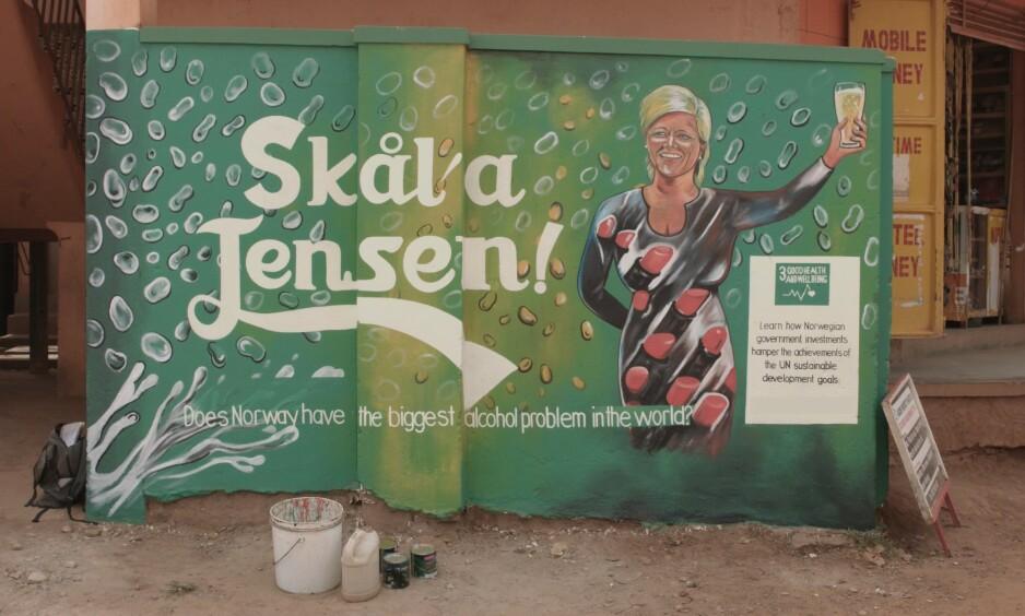 VEGGMALERI: «Skål'a Jensen!» er inspirert av en tale finansminister Siv Jensen holdt etter stortingsvalget i 2013. Maleriet er ett av flere som er malt på vegger i Uganda for å markere at Oljefondet bør trekke seg ut av alkoholindustrien. Foto: FORUT