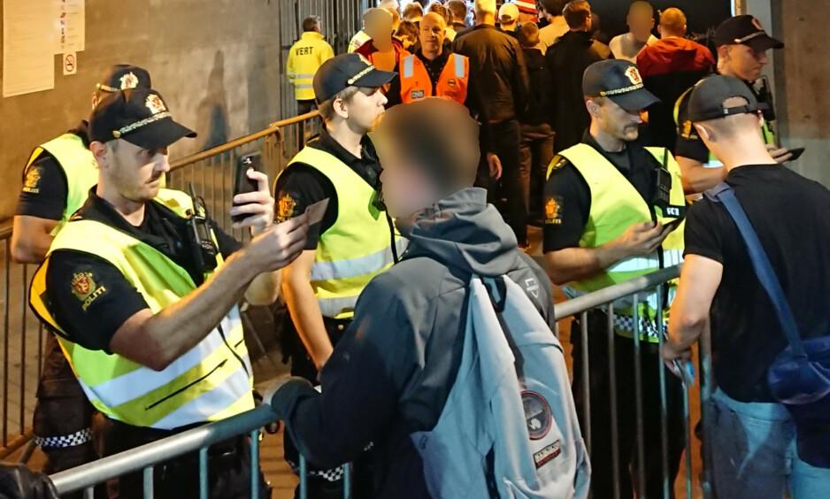 SKAPER REAKSJONER: Bortesupportere måtte vise fram personalia og ble avbildet på vei ut av Åråsen søndag. Foto: Tipser.