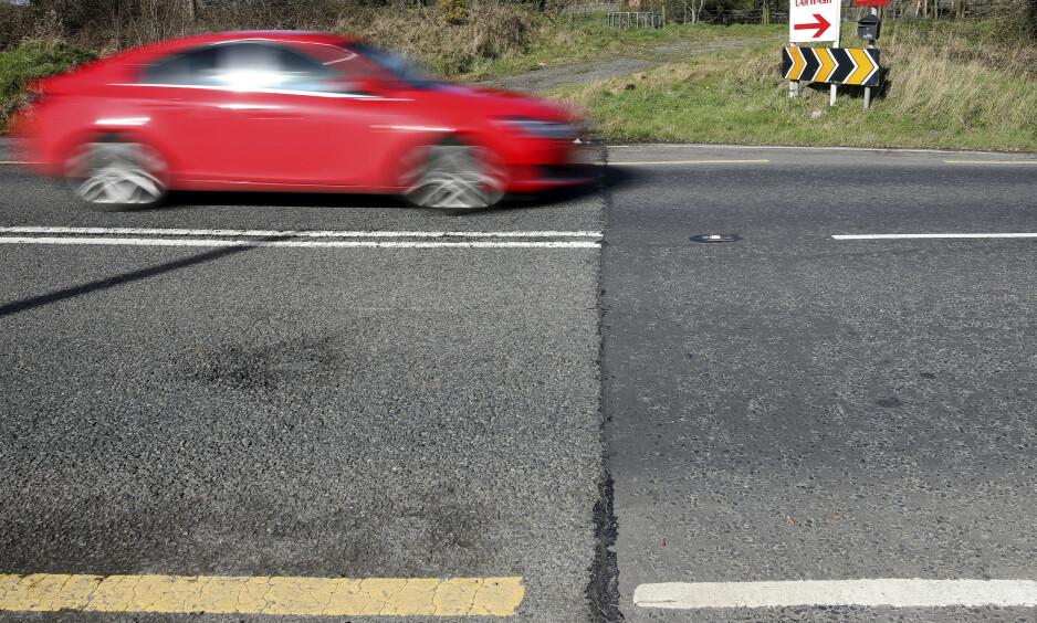 PROBLEM-GRENSA: Dette er stedet hvor britisk og nord-irsk asfalt (t.h.) møter europeisk og irsk asfalt. Det er også det eneste som skiller de to landene. Det kan endre seg hvis Storbritannia forlater EU uten en avtale. Foto: Reuters / NTB Scanpix