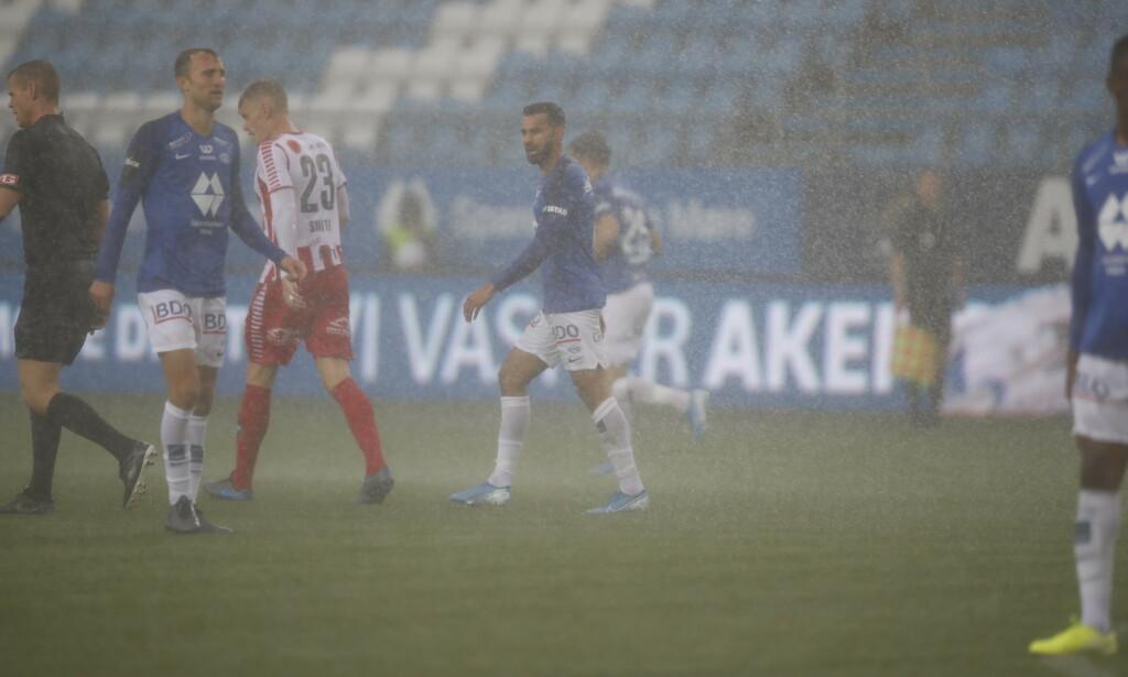 REGN OG VIND: Spillerne sliter i været. Foto: Tore Meek / NTB scanpix