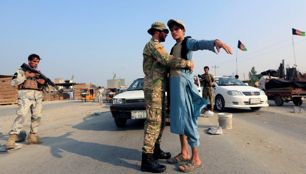 HØYSPENN: En afghansk politimann kroppsvisiterer en bilpassasjer ved et sjekkpunkt i Jalalabad, Afghanistan, denne uka. Foto: REUTERS/Parwiz