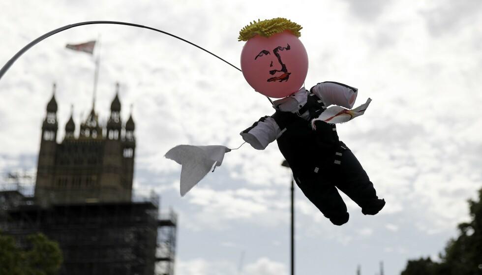 LØKKE RUNDT HALSEN: Boris Johnson hengende i dokkeversjon i en demonstrasjon foran Parlamentet i London fredag. Demonstrasjonene og uttrykksformene er ventet å øke i styrke i Manchester ved åpningen av landsmøtet i det konservative partiet søndag. Foto: Tolga Akmen / AFP / NTB Scanpix