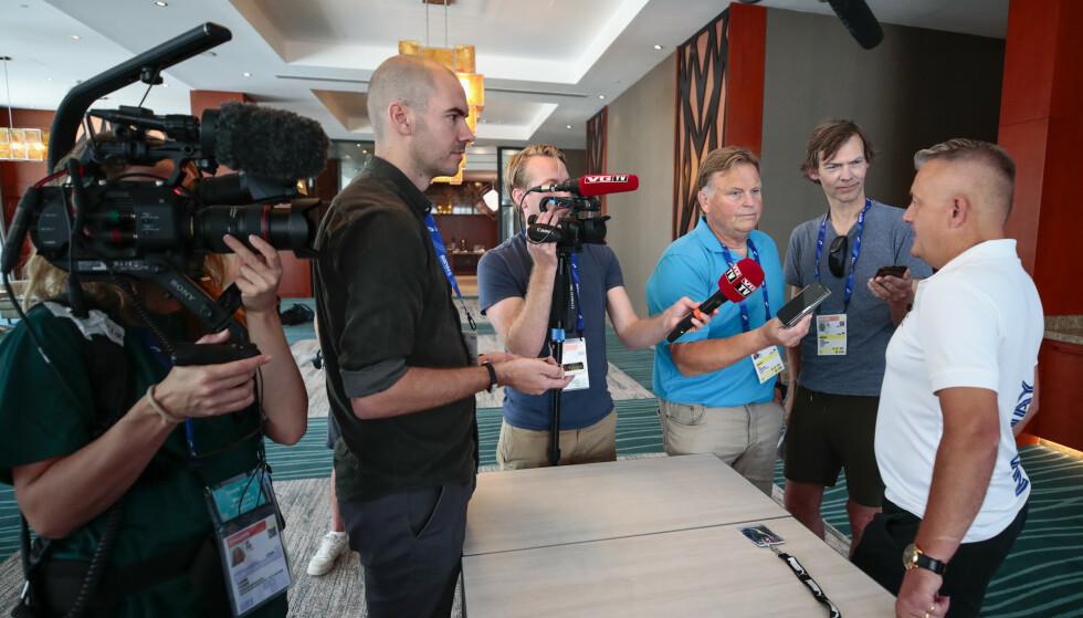 EN ETTERTRAKTET MANN: Gjert Ingebrigtsen er omkranset av norske journalister i Doha i dag, og får stadig flere henvendelser fra internasjonale medier etter suksessen. Foto: Lise Åserud / NTB Scanpix