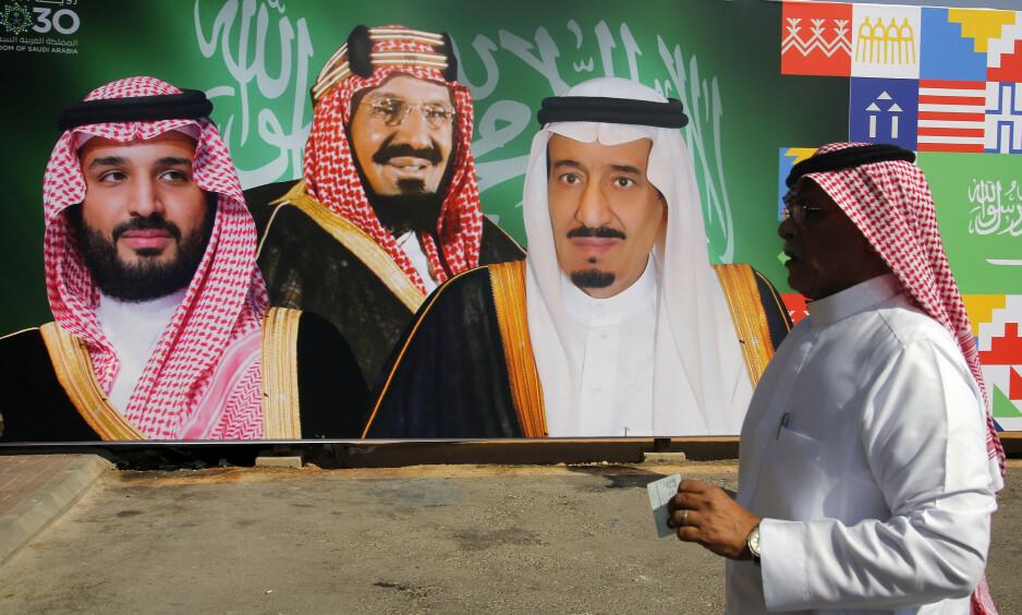 NYTT INTERVJU: En mann går forbi en plakat der kronprins Mohammed bin Salman (t.v), Saudi-grunnlegger og konge Abdul Aziz Al Saud (midten) og kong Salman (t.h) smiler på en privat flyplass i byen Riyadh. Foto: Amr Nabil / Ap / Scanpix
