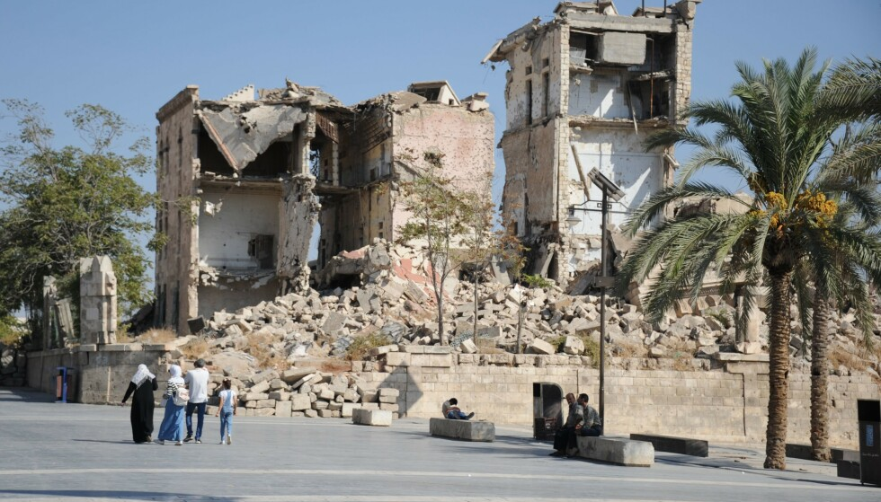 I RUINER: Bildet viser folk som passerer en skadet bygning i gamlebyen i Aleppo i september 2019. Syria lider ennå under den svært blodige krigen, som fortsatt pågår i deler av landet. Foto: Maxime Popov / AFP/NTB Scanpix