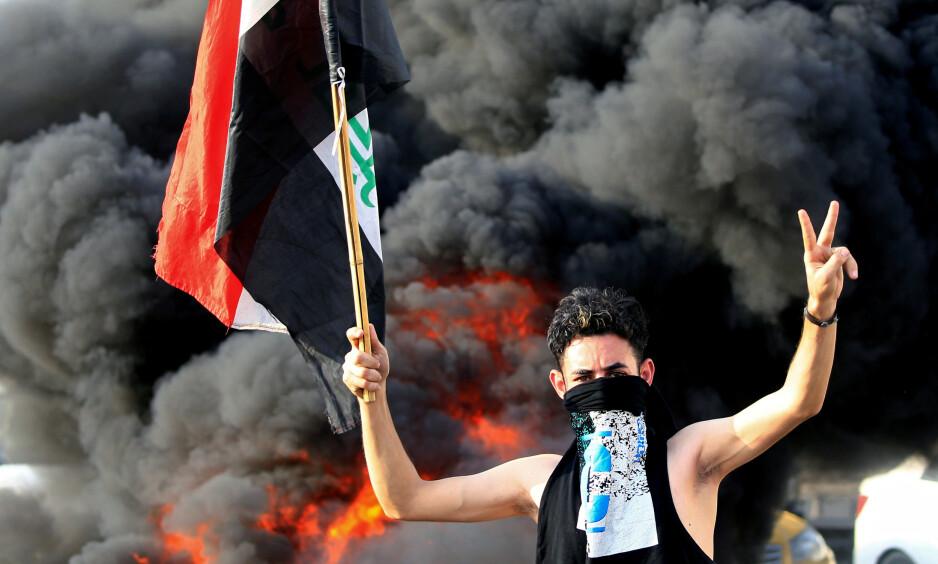 KREVER ENDRING: En av de mange tusen demonstrantene i hovedstaden Bagdad. Men de siste dagene har det vært voldsomme demonstrasjoner i en rekke byer i landet. Minst ni personer skal være drept. Demonstrantene raser over høy arbeidsledighet, korrupsjon og dårlige tjenester. Foto: Thaier al-Sudani / Reuters / Scanpix