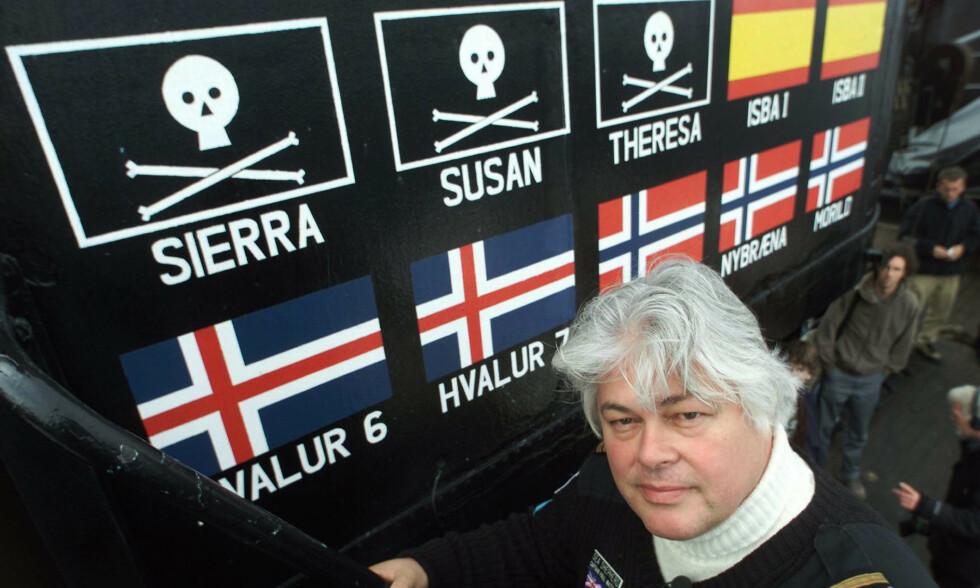 TROFÉVEGGEN: Kaptein Paul Watson poserer foran skryteveggen på skipet «Ocean Warrior» i 2000. Flaggene viser hvor mange fangstskip Watson hevder å ha senket. Foto: NTB