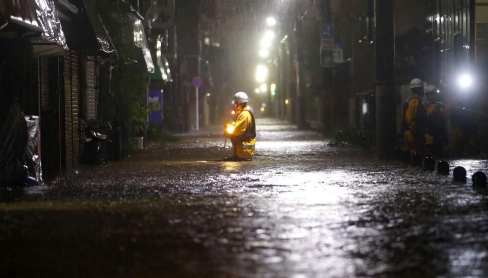 OVERSVØMT: En brannmann i Tokyo inspiserer en gate som er oversvømt etter tyfonen Hagibis sine herjinger. Foto: Kyodo/REUTERS/NTB Scanpix.