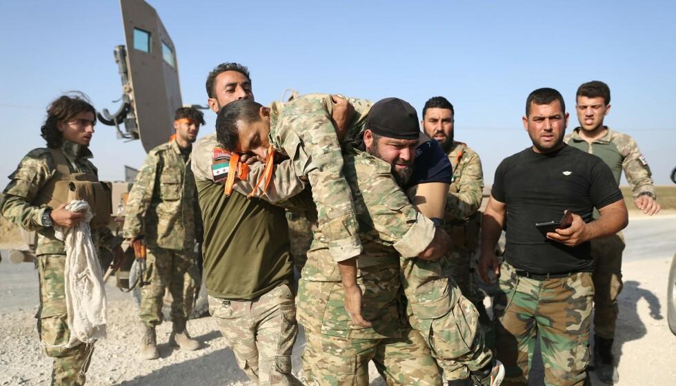 RAS AL-AIN: Den strategisk viktige grensebyen er blant områdene hvor det har pågått hardest kamper. Her bærer tyrkiskstøttede soldater vekk en skadet medsoldat i den pågende kampene. Tyrkia har kommet stadig lengen inn i Syria, og har snart tatt over hele den planlagte buffersonen. Foto: Nazeer Al-khatib / AFP/NTB Scanpix
