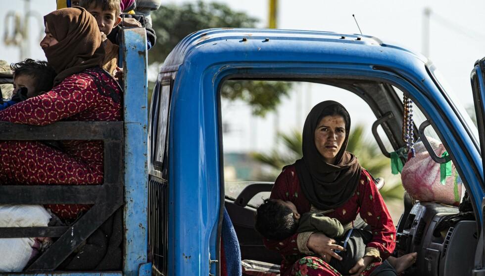 PÅ FLUKT: Ifølge tall fra FN tirsdag er nå 190 000 mennesker drevet på flukt i Syria som følge av den pågående tyrkiske offensiven. Rundt 70 000 av dem er barn. Her flykter en syrisk familie byen Ras al-Ain, der det i dagesvis har pågått harde kamper mellom kurderne og Tyrkia og deres allierte grupper. Kurderne holder fortsatt grensebyen. Foto: Delil SOULEIMAN / AFP / NTB Scanpix