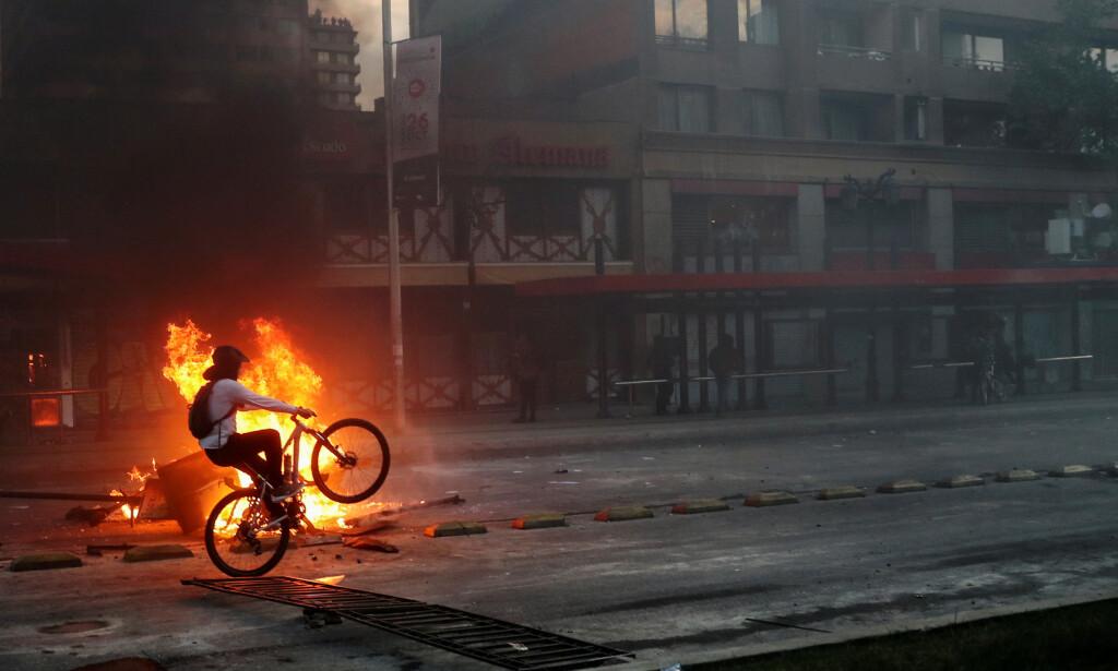 OPPTØYER: En demonstrant sykler forbi en påtent brann mens mange chilienere er ute i gatene og protesterer over økte metro-billetter i Santiago, Chile. Foto: Ivan Alvarado / Reuters / Scanpix