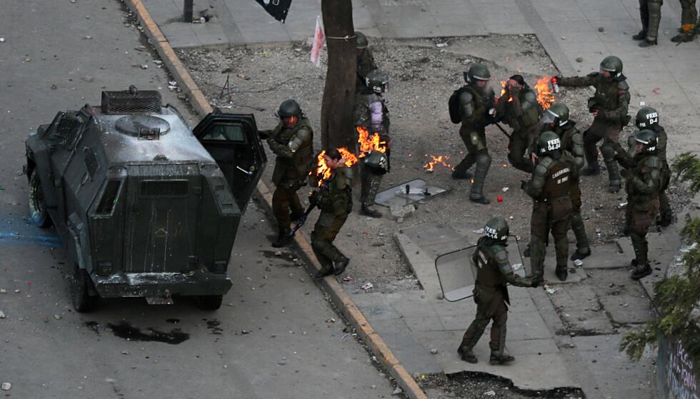 STRØMMET TIL: Andre politifolk strømmet til for å hjelpe, da de to politikvinnene kjempet for å slukket brannen i hode og nakke-regionen. Foto: NTB Scanpix/Reuters/Ivan Alvarado
