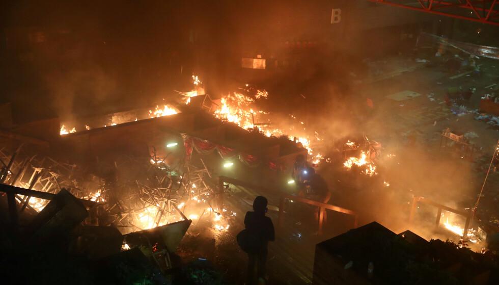 ENORME ØDELEGGELSER: En demonstrant ser at flammene brenner bort deler av det polytekniske universitetet i Hongkong i kveld. Foto: Athit Perawongmetha / Reuters / NTB Scanpix