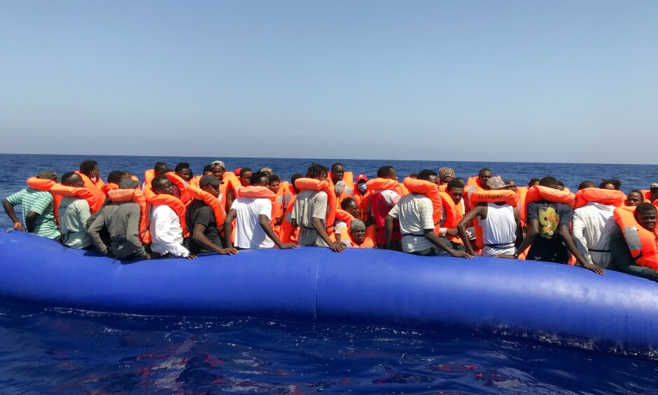 BLIR REDDET: 81 personer blir her snart hentet opp fra den overfylte gummibåten og over i den norsk-eide redningsbåten Ocean Viking, som drives av Leger Uten Grenser og en fransk organisasjon. Foto: Anne Chaon / AFP / NTB Scanpix