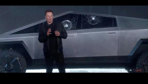 BILFOTO FOR HISTORIEN: En tilsynelatende forfjamset Elon Musk foran de to knuste bilrutene, som ble garantert skuddsikre. Foto: Tesla/Reuters.
