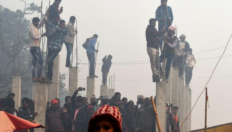 TILSKUERE: Flere tilskuere klatret opp på påler for å se seremonien. Foto: AFP