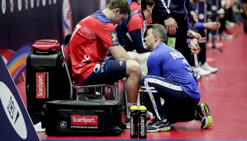 FIKK BEHANDLING: Magnus Abelvik Rød ble skadet under kampen mellom Norge og Ungarn i Malmø Arena. Harald Markussen pleier Magnus. Foto: Vidar Ruud / NTB Scanpix