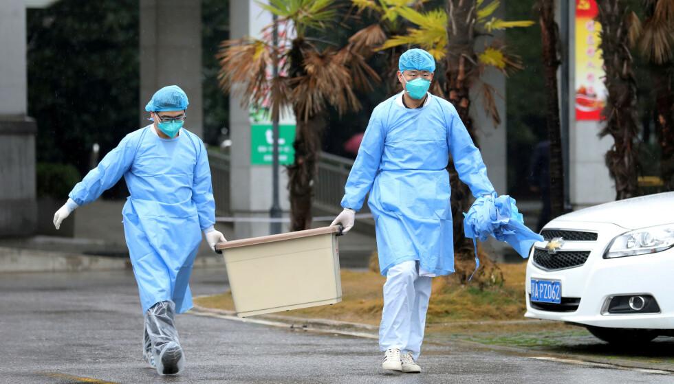 FLERE INNLAGT: Helsepersonell bærer en boks ut av sykehuset der flere pasienter for tiden er innlagt for behandling av Coronavirus-smitte i Wuhan i Kina. Foto: Reuters / NTB scanpix