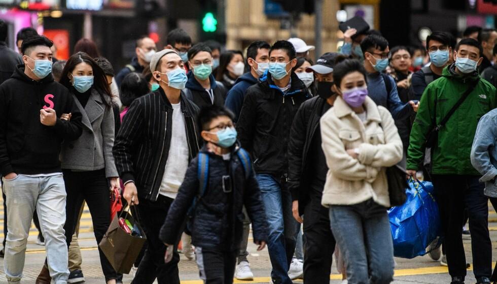 WUHAN: Fotgjengere med munnbind avbildet i Wuhan 27. januar 2020. Det var her viruset på oppdaget i begynnelsen av januar. Kinesiske myndigheter tror at lungeviruset kan ha smittet mennesker via et marked der det er blitt solgt ville dyr. Foto: Anthony Wallace / AFP / NTB Scanpix