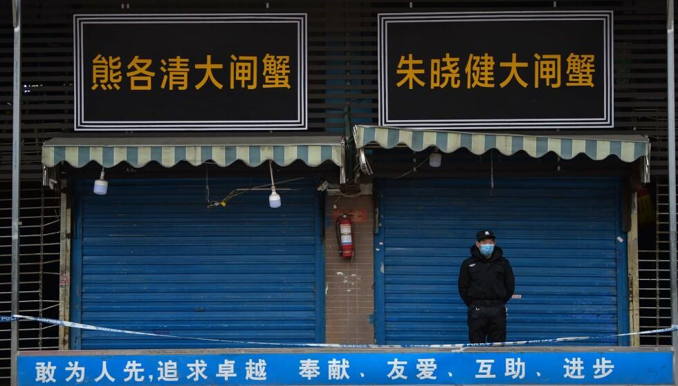 STARTET HER: Coronaviruset skal ha startet sin smitteferd på dette sjømat-markedet i millionbyen Wuhan. Her holder en sikkerhetsvakt utkikk utenfor det nå avstengte markedet. Foto: Hector RETAMAL / AFP / NTB scanpix