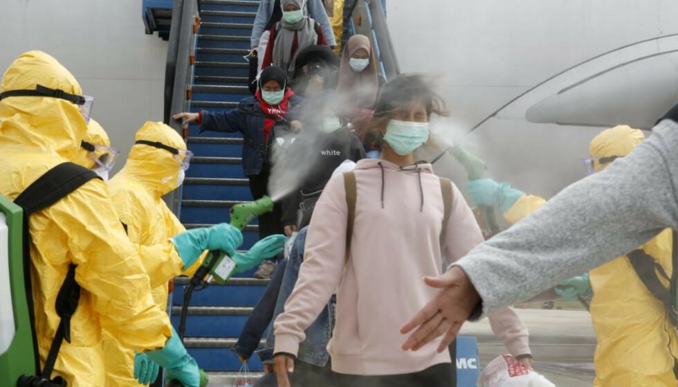 DESINFISERER: Helsepersonell spyler desinfiserende midler på passasjerer som ankommer Indonesia fra den kinesiske virusbyen Wuhan. Foto: Foto. Antara / Reuters / NTB scanpix