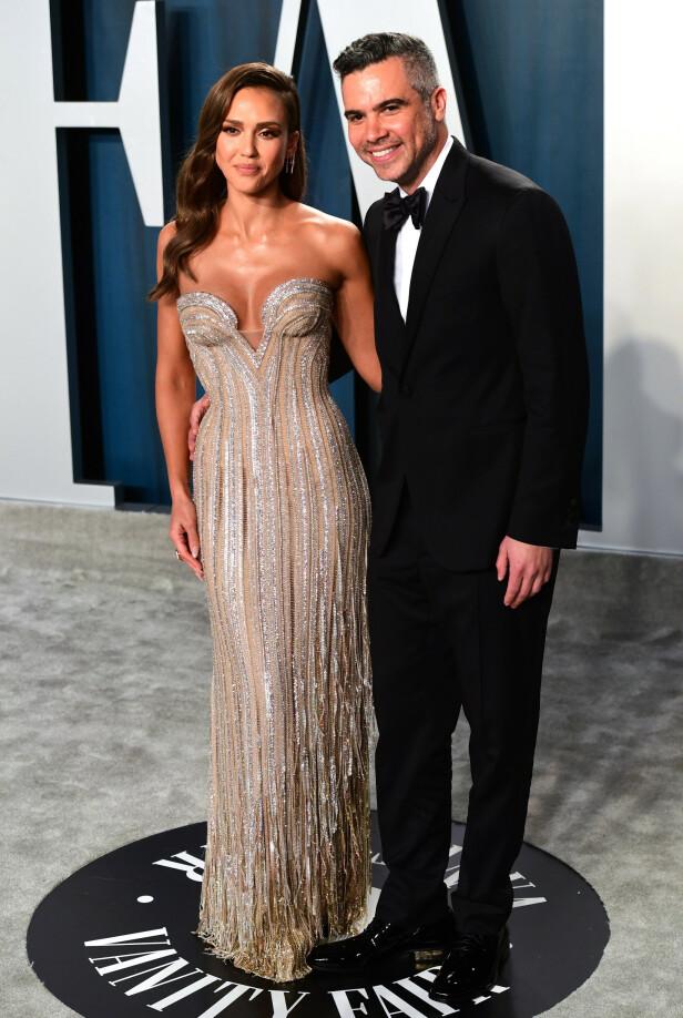 GLITRET: Skuespiller Jessica Alba poserte foran kameraene i en glitrende kjole fra Versace sammen med ektemannen Cash Warren. Foto: NTB Scanpix