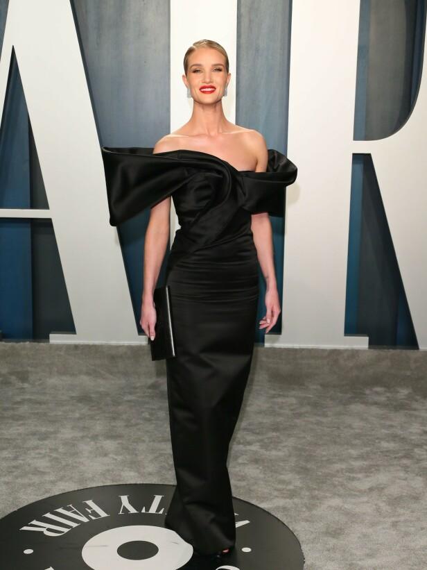 DUKKET OPP: Modell Rosie Huntington-Whiteley strålte i en sort stroppeløs satengkjole. Foto: NTB Scanpix