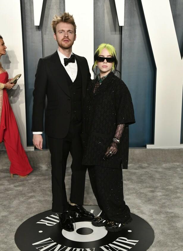 GLITRET IFØRT LUKSUSMERKE: Artist Billie Eilish poserte foran kameraene iført glitrende klær fra Gucci. Artisten kom sammen med storebroren Finneas. Foto: NTB Scanpix